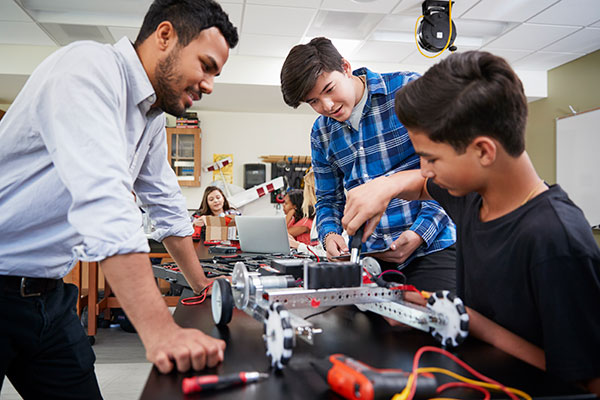 Students working on a robot under supervision.